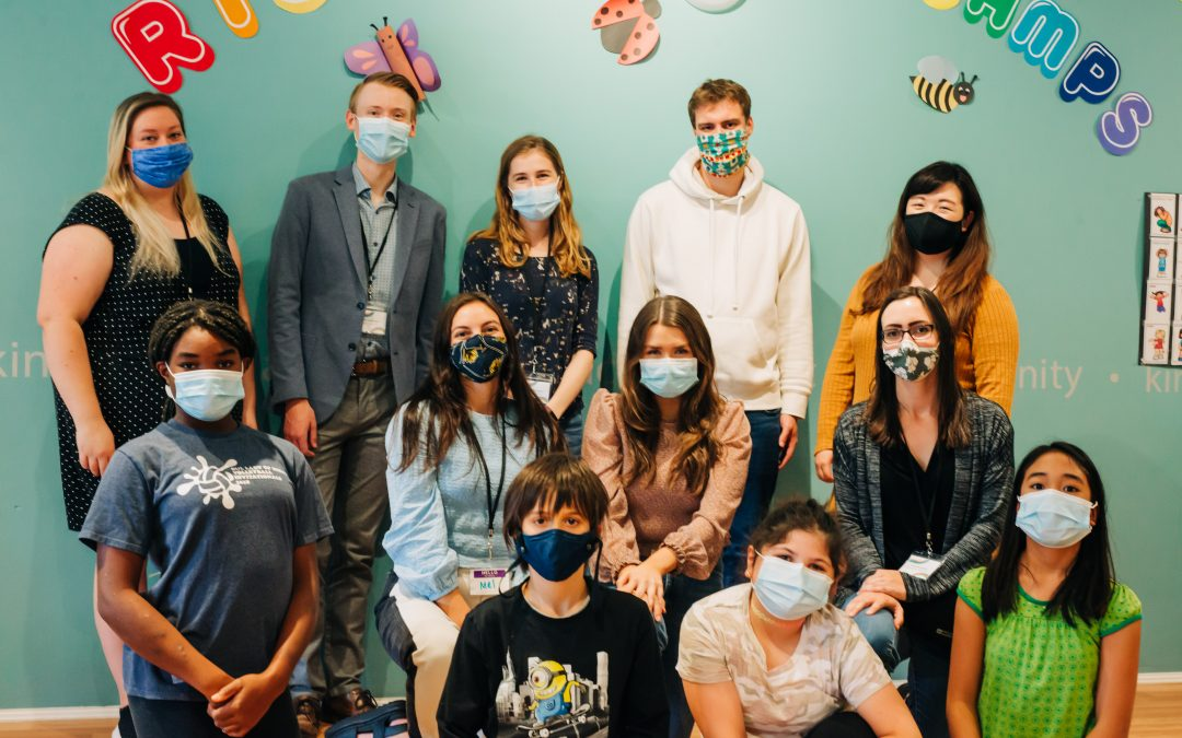 A group of 8 adults and 4 kids pose at LDS with face masks on