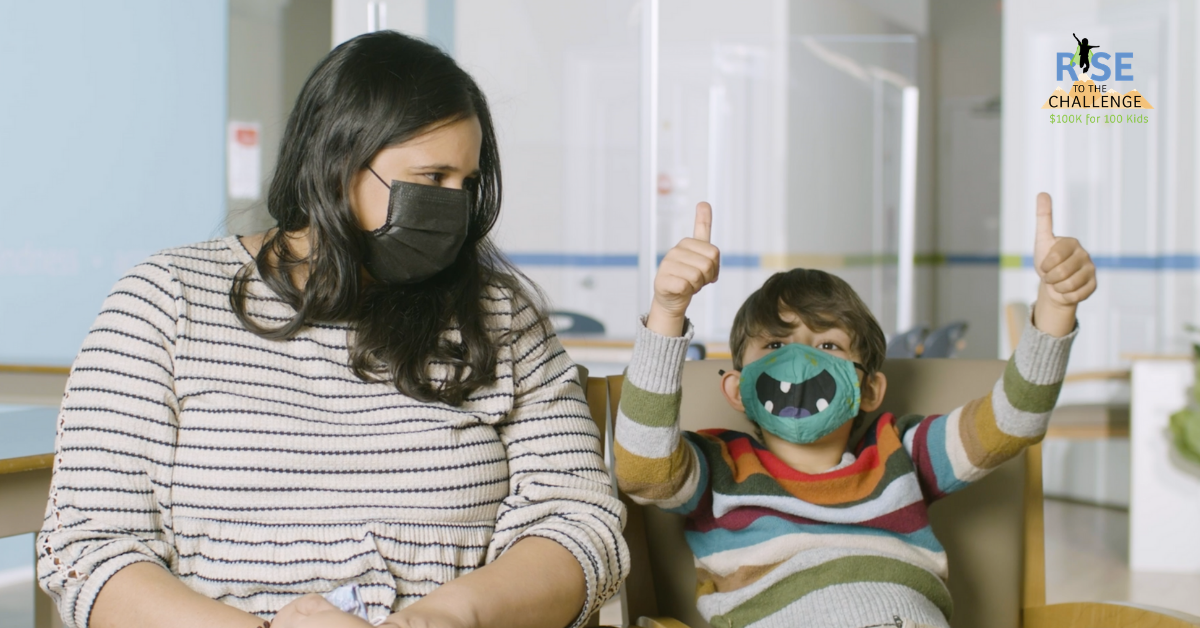 Mother with mask looks at child with monster mask on as he gives two thumbs up.
