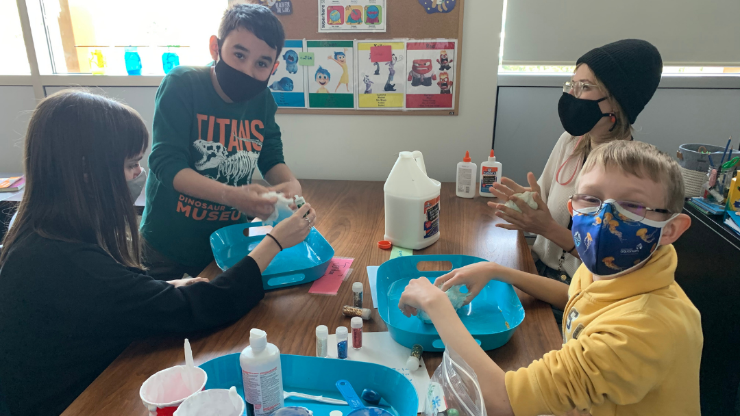 Two male students and two female teachers all wearing masks sit around table making slime.